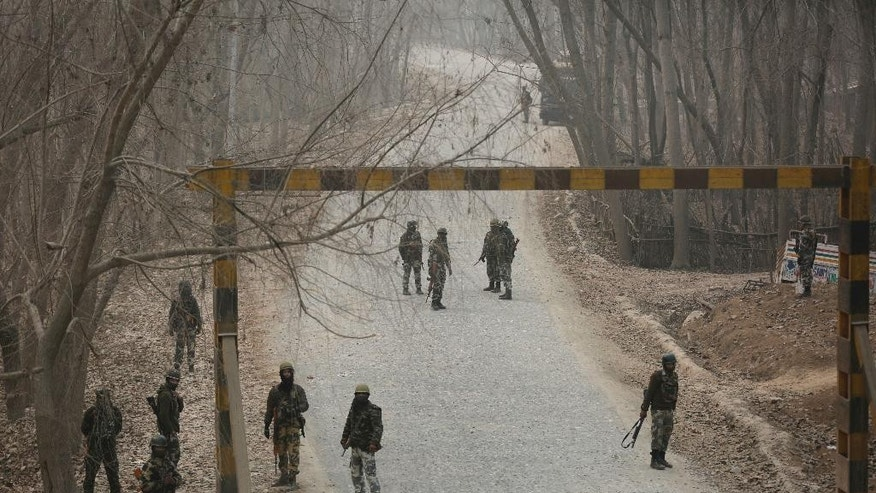 Indian soldiers block a road near the site of a gun battle at Arwani, 55 kilometres (34 miles) south of Srinagar, Indian-controlled Kashmir, Thursday, Dec. 8, 2016. Dozens of civilians in Indian-controlled Kashmir were injured on Thursday as anti-India clashes erupted in the disputed region following a gun battle between rebels and government forces, officials and witnesses said. (AP Photo/Mukhtar Khan)