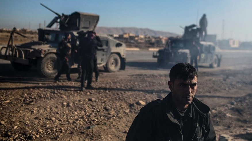 An Iraqi Special Forces member stands near the main road from Erbil to Mosul with his unit, in the village of Bartala, Iraq, Wednesday, Dec. 7, 2016. A senior Iraqi commander says special forces captured a new neighborhood from Islamic State militants in eastern Mosul, the latest gain in a massive government military operation now in its seventh week. (AP Photo/Manu Brabo)