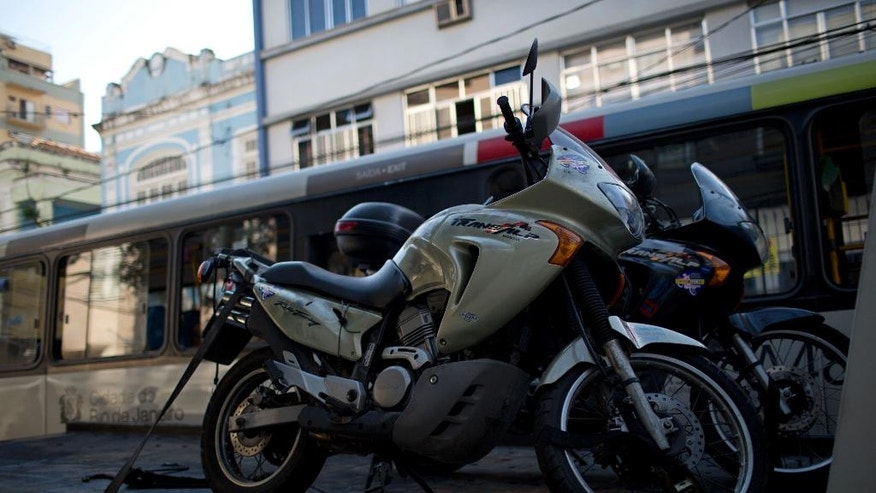 Two motorcycles that belonged to Italian tourists that were touring South America are picked up and taken away by authorities in Rio de Janeiro, Brazil, Thursday, Dec.8, 2016. Police say Italian tourist Roberto Bardella was killed by alleged drug traffickers as he drove his bike by one of the entrance of the Morro dos Prazeres favela. Rio de Janeiro police said another Italian tourist named Rino Polato was found early in the day unharmed at an entrance to the Morro dos Prazeres favela. (AP Photo/Silvia Izquierdo)