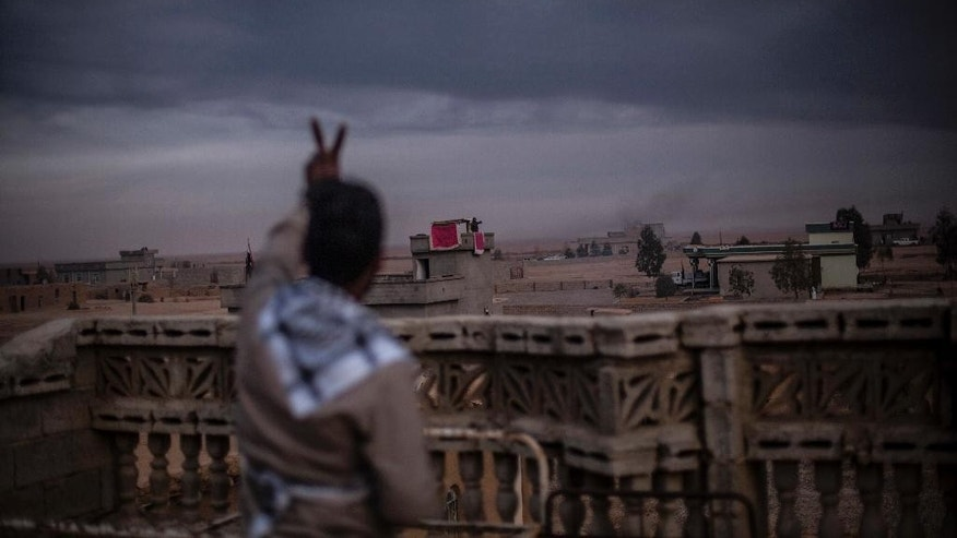 A member of the Sunna militia salutes a comrade in another roof making the victory sign in Sheyalat village, around 70Km from Mosul, Iraq, Thursday, Dec. 8, 2016.(AP Photo/Manu Brabo)