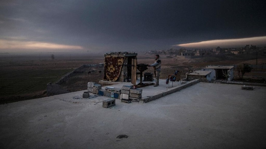 A member of the Sunna militia stands on guard atop the roof of a building in Haji Ali Sheyalat village, around 70Km from Mosul, Iraq, Thursday, Dec. 8, 2016.b(AP Photo/Manu Brabo)