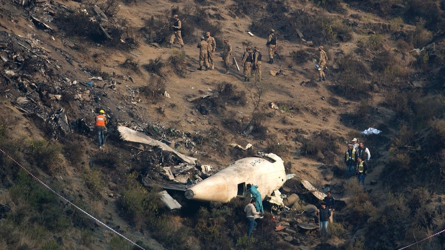 Pakistani investigators examine the wreckage of a passenger plane crashed in the village of Gug, Pakistan Thursday, Dec. 8, 2016.