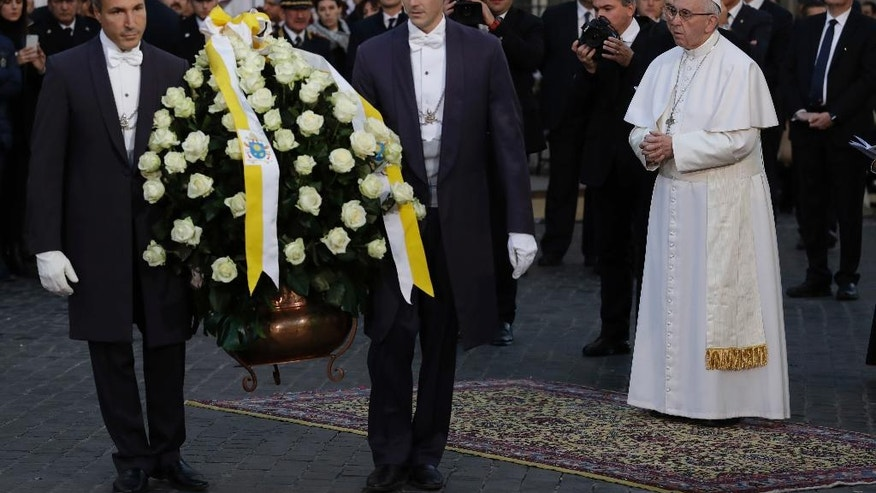 Pope Francis prays as flowers are being laid to pay respect to the statue of the Vergin Mary in downtown Rome, Thursday, Dec. 8, 2016, on occasion of the Immaculate Conception feast. (AP Photo/Andrew Medichini)