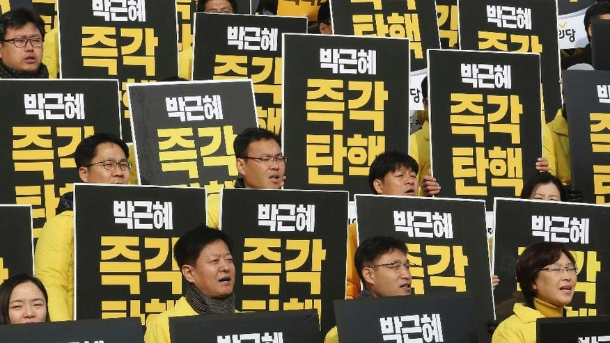 "Lawmakers and members of opposition Justice Party shout slogans during a rally demanding the impeachment of South Korean President Park Geun-hye at the National Assembly in Seoul, South Korea, Thursday, Dec. 8, 2016. Park, who faces the political fight of her life as lawmakers attempt to force her from office over prosecution claims that she helped a confidante extort money and favors from companies and manipulate state affairs. The signs read: ""Impeach Park Geun-hye immediately."" (AP Photo/Ahn Young-joon)"