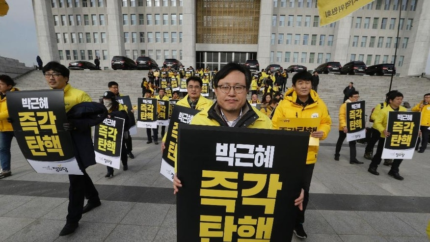 "Lawmakers and members of opposition Justice Party with banners march during a rally demanding the impeachment of South Korean President Park Geun-hye at the National Assembly in Seoul, South Korea, Thursday, Dec. 8, 2016. Park aces the political fight of her life as lawmakers attempt to force her from office over prosecution claims that she helped a confidante extort money and favors from companies and manipulate state affairs. The signs read: ""Impeach Park Geun-hye immediately."" (AP Photo/Ahn Young-joon)"