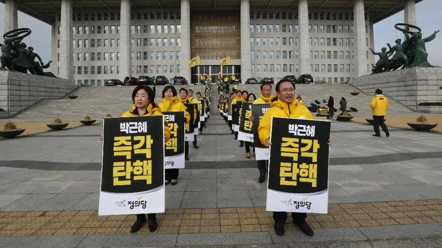 "Lawmakers and members of opposition Justice Party with signs stand during a rally demanding the impeachment of South Korean President Park Geun-hye at the National Assembly in Seoul, South Korea, Thursday, Dec. 8, 2016. Park aces the political fight of her life as lawmakers attempt to force her from office over prosecution claims that she helped a confidante extort money and favors from companies and manipulate state affairs. The signs read: ""Impeach Park Geun-hye immediately."" (AP Photo/Ahn Young-joon)"