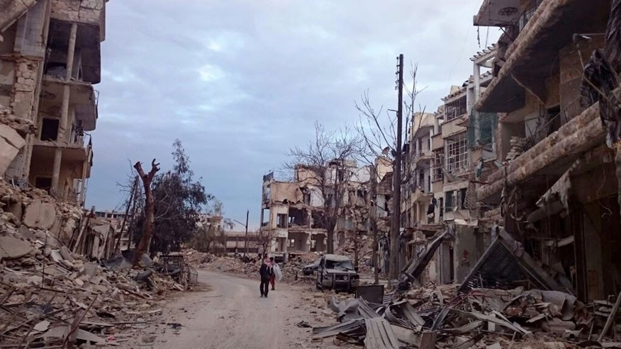 In this photo, courtesy of Wissam Zarqa, a Syrian English teacher and vocal anti-government critic, men walk past damaged buildings and shops in the eastern Aleppo neighborhood of al-Mashhad, Syria, Thursday, Dec. 8, 2016. Government troops and allied militiamen have been advancing swiftly into the once rebel-controlled eastern Aleppo enclave as defenses of the opposition fighters buckle. (Courtesy of Wissam Zarqa, via AP)