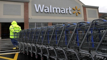 FILE - in this Nov. 13, 2012 photo a worker pulls a line of shopping carts toward a Wal-Mart store in North Kingstown, R.I.  Wal-Mart reported improved customer traffic and an uptick in a key sales figure as it topped earnings expectations in the third quarter, even as a stronger dollar pressured its performance overseas. Its shares edged up more than 2 percent in premarket trading Tuesday, Nov. 17, 2015 after it detailed results from the quarter that ended Oct. 31. (AP Photo/Steven Senne)