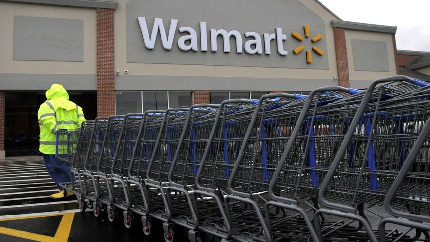 Worker pulls a line of shopping carts toward a Wal-Mart store in North Kingstown, R.I.