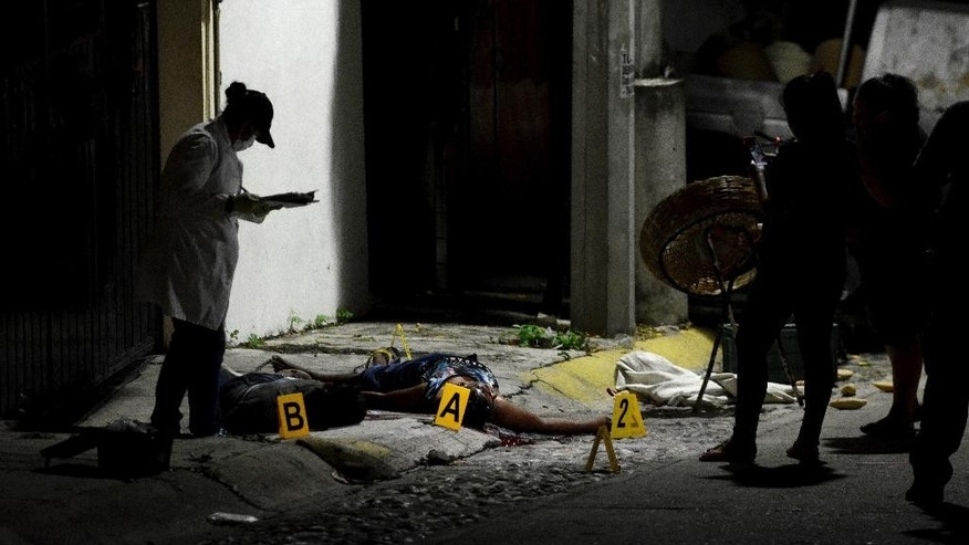 "A forensic medic investigates the crime scene where two people were shot dead by unidentified attackers in Acapulco, Mexico, Thursday, Dec. 8, 2016. The area has been the scene of increasing violence in recent months. The U.S. Embassy has issued a travel advisory that reads: ""In Ixtapa-Zihuatanejo, U.S. government personnel must remain in tourist areas."" Guerrero state has seen an uptick in killings, with gangs often sending messages to rivals by dumping bodies. (AP Photo/Bernandino Hernandez)"