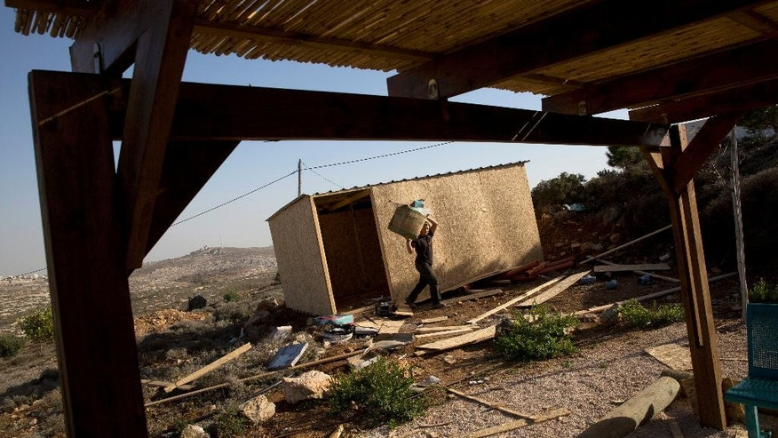In this photo taken Tuesday, Dec. 6, 2016, a Jewish settler youth carries a box near a new structure in Amona, an unauthorized Israeli outpost in the West Bank, east of the Palestinian town of Ramallah. Residents of the Amona settlement outpost in the West Bank are digging in for a fight to the finish despite an impending court-ordered evacuation. With the Dec. 25 evacuation date approaching, Israel's pro-settler government is scrambling to find a solution, fearing a showdown between extremist settlers and security forces.(AP Photo/Sebastian Scheiner)