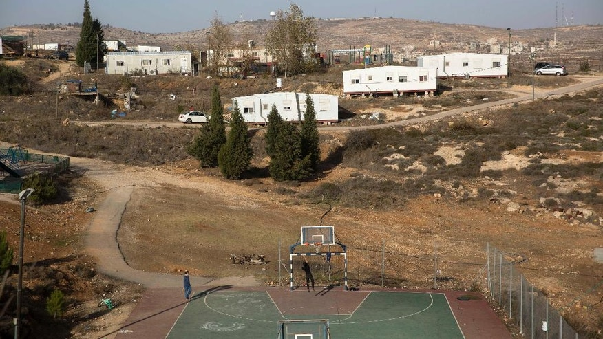 In this photo taken Tuesday, Dec. 6, 2016, Jewish settler youths play basketball in Amona, an unauthorized Israeli outpost in the West Bank, east of the Palestinian town of Ramallah. Residents of the Amona settlement outpost in the West Bank are digging in for a fight to the finish despite an impending court-ordered evacuation. With the Dec. 25 evacuation date approaching, Israel's pro-settler government is scrambling to find a solution, fearing a showdown between extremist settlers and security forces.(AP Photo/Sebastian Scheiner)