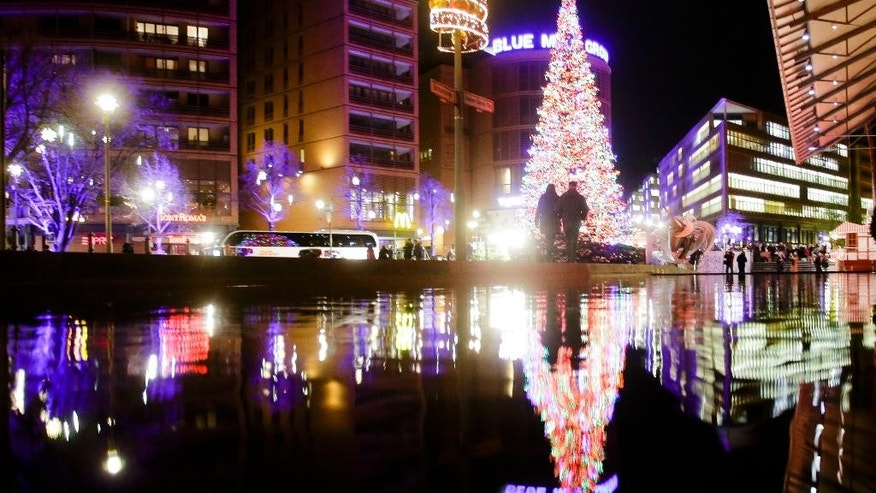 Visitors walk in front of the illuminated Christmas tree near the Christmas market at the Potsdamer Platz square in Berlin, Germany, Thursday, Dec. 8, 2016. (AP Photo/Markus Schreiber)