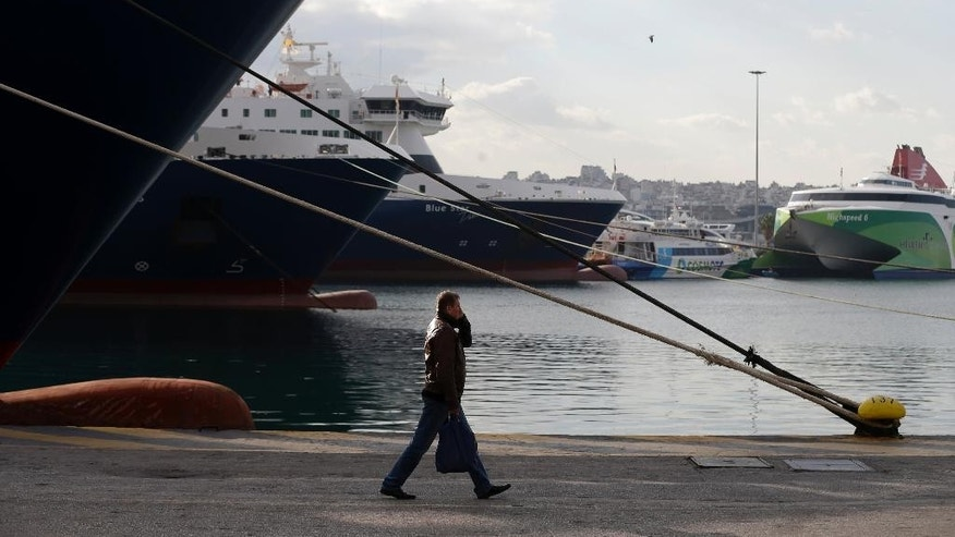 A man walks by docked ferries during the seventh day of strike by seamen's unions at the port of Piraeus near Athens, Thursday, Dec. 8, 2016. Ferry crews continue their strike as Greece's biggest labor unions have called a general strike for Thursday, to protest further tax hikes and labor reforms demanded by the country's bailout creditors. (AP Photo/Thanassis Stavrakis)