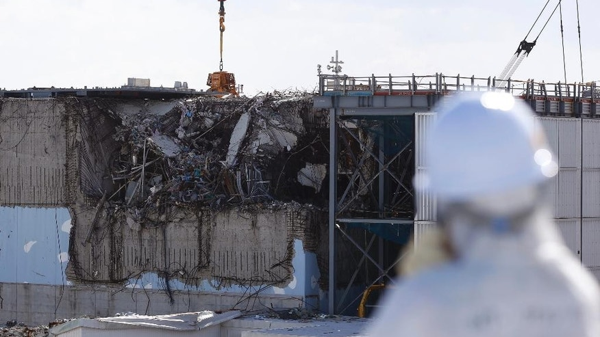 FILE - In this Feb. 10, 2016 file photo, a member of the media tour group wearing a protective suit and a mask looks at the No. 3 reactor building at Tokyo Electric Power Co's (TEPCO) tsunami-crippled Fukushima Dai-ichi nuclear power plant in Okuma, Fukushima Prefecture, northeastern Japan, one month before Japan marks the fifth anniversary of a devastating earthquake and tsunami that left nearly 19,000 people dead or missing, turned coastal communities into wasteland and triggered a nuclear crisis. A cost estimate to clean up Japan's wrecked Fukushima nuclear plant has doubled to nearly 22 trillion yen ($190 billion), with decommissioning costs expected to continue to rise, according to a government panel Friday, Dec. 9, 2016. (Toru Hanai/Pool Photo via AP, File)