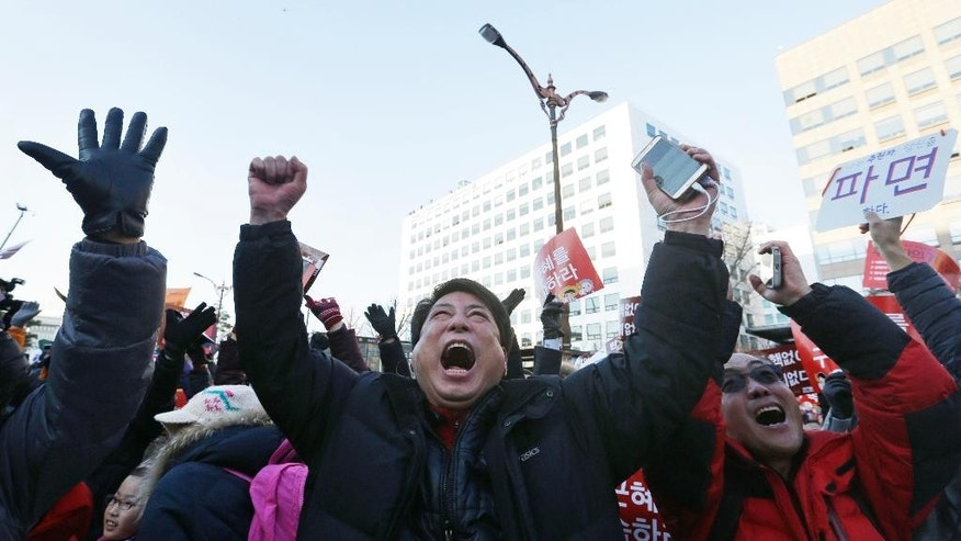 Protesters celebrate after hearing the news of President Park Geun-hye's impeachment in front of the National Assembly in Seoul, South Korea, Friday, Dec. 9, 2016. South Korean lawmakers on Friday voted to impeach Park, a stunning and swift fall for the country's first female leader amid protests that drew millions into the streets in united fury. (AP Photo/Ahn Young-joon)