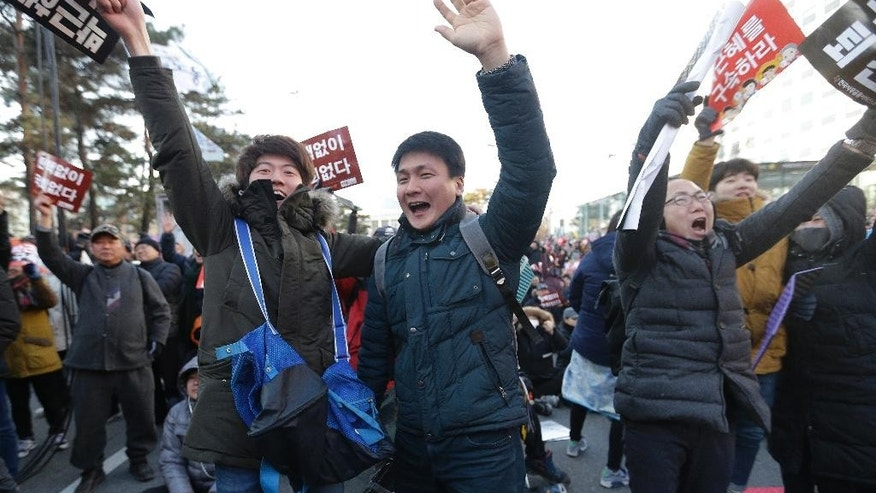 Protesters celebrate after hearing the news of President Park Geun-hye's impeachment in front of the National Assembly in Seoul, South Korea, Friday, Dec. 9, 2016. South Korean lawmakers on Friday voted to impeach Park, a stunning and swift fall for the country's first female leader amid protests that drew millions into the streets in united fury.(AP Photo/Ahn Young-joon)