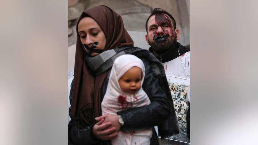 A Turkish woman from pro-Islamic groups holds a painted doll depicting dead Syrian babies as they protest against the war in Aleppo, Syria, in Istanbul, Thursday, Dec. 8, 2016. Aleppo shakes with explosions and gunfire day and night in both the government and rebel sides. (AP Photo/Emrah Gurel)