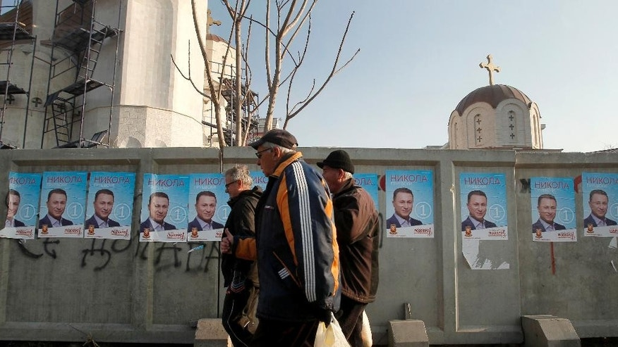 Men walk past election posters of Nikola Gruevski, the leader of the ruing VMRO-DPMNE party, set on a fence along a street in Macedonia's capital Skopje, Friday, Dec. 9, 2016. Eleven political parties and coalitions in Macedonia are ending their campaigns ahead of general elections on Sunday. (AP Photo/Boris Grdanoski)