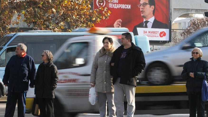 People stand on a street where an election poster of the opposition SDSM party candidate Stevo Pendarovski is displayed above, in Macedonia's capital Skopje, Friday, Dec. 9, 2016. Eleven political parties and coalitions in Macedonia are ending their campaigns ahead of general elections on Sunday. (AP Photo/Boris Grdanoski)