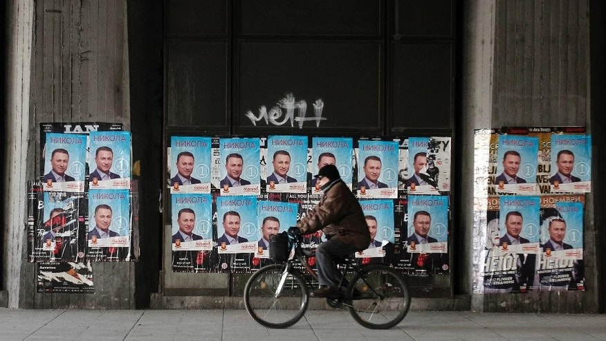 A man rides a bicycle past election posters of Nikola Gruevski, the leader of the ruing VMRO-DPMNE party, set along a street in Macedonia's capital Skopje, Friday, Dec. 9, 2016. Eleven political parties and coalitions in Macedonia are ending their campaigns ahead of general elections on Sunday. (AP Photo/Boris Grdanoski)