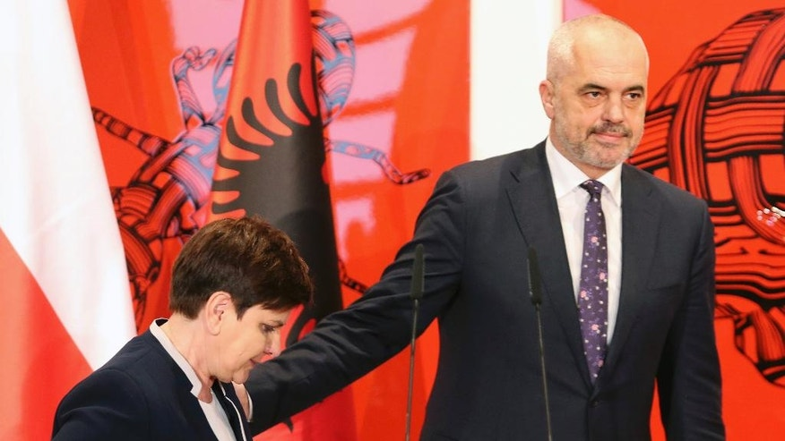 Albanian Prime Minister Edi Rama, right, arrives with his Polish counterpart Beata Szydlo for a press conference in Tirana, Friday, Dec. 9, 2016. Szydlo is in Albania for top-level talks on European security and integration and on bilateral cooperation in the economy. (AP Photo/Hektor Pustina)