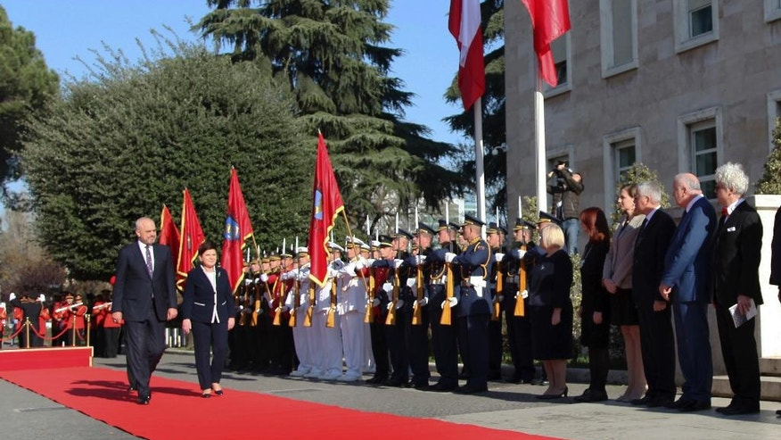 Albania Prime Minister Edi Rama, left, and his Polish counterpart Beata Szydlo review the honor guard in Tirana, Friday, Dec. 9, 2016. Szydlo is in Albania for talks on European security and integration and on bilateral cooperation in the economy. (AP Photo/Hektor Pustina)