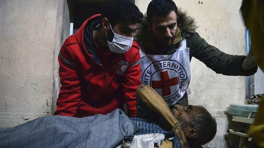 This Wednesday, Dec. 7, 2016 photo, released by the International Committee for the Red Cross, shows members of the Syrian Arab Red Crescent laying a patient on stretcher after taking him out of a medical facility in the Old City of Aleppo, Syria. The ICRC said it evacuated 148 disabled or civilians in need of urgent care from the facility, now under Syrian government control. ICRC said in a statement Thursday the evacuation was possible after fighting calmed down in the area. (Syrian Arab Red Crescent/Noor Hazouri via AP)