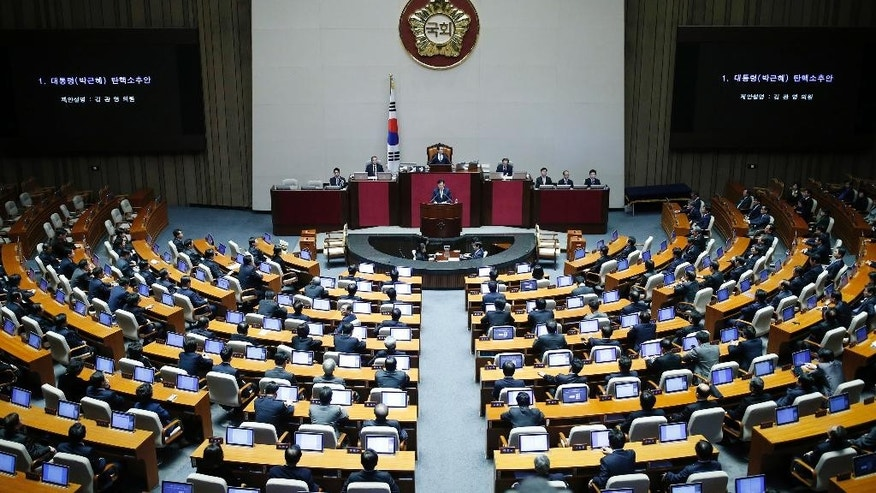 South Korea's lawmakers attend a plenary session to vote on the impeachment bill of President Park Geun-hye at the National Assembly in Seoul Friday, Dec. 9, 2016. South Korean lawmakers on Friday impeached Park, a stunning and swift fall for the country's first female leader amid protests that drew millions into the streets in united fury. (Kim Hong-Ji/Pool Photo via AP)