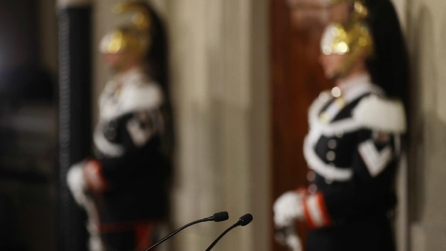 Courassier presidential guards stand next the studio of Italian president Sergio Mattarella, with in foreground the microphones from where politicians talk to the media at the Quirinal Palace in Rome, Thursday, Dec. 8, 2016. President Mattarella starts today a three-day round of talks with political leaders to try and form a new government. (AP Photo/Gregorio Borgia)