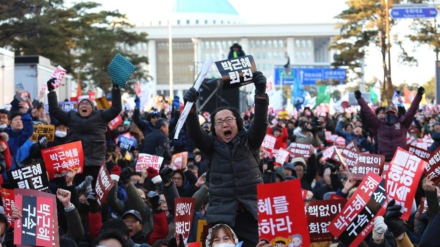 "Protesters celebrate after hearing the President Park Geun-hye's impeachment in front of the National Assembly in Seoul, South Korea, Friday, Dec. 9, 2016. South Korean lawmakers on Friday voted to impeach Park, a stunning and swift fall for the country's first female leader amid protests that drew millions into the streets in united fury. The sign reads ""Impeach Park Geun-hye immediately."" (AP Photo/Ahn Young-joon)"