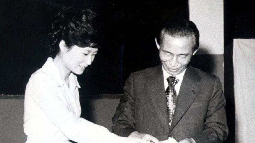 FILE - In this 1977 file photo, then South Korean President Park Chung-hee, right, and his daughter Park Geun-hye cast ballots in Seoul, South Korea. Throughout a political career that saw a triumphant return as South Korea's first female president to the palatial Blue House where she'd lived as a girl, Park Geun-hye could always rely on the devotion many felt for her late dictator father. In the end, after millions of protesters swarmed the streets around her presidential fortress, even the conservative adulation that had been her political bedrock failed to save her from impeachment. (AP Photo/Yonhap, File) KOREA OUT
