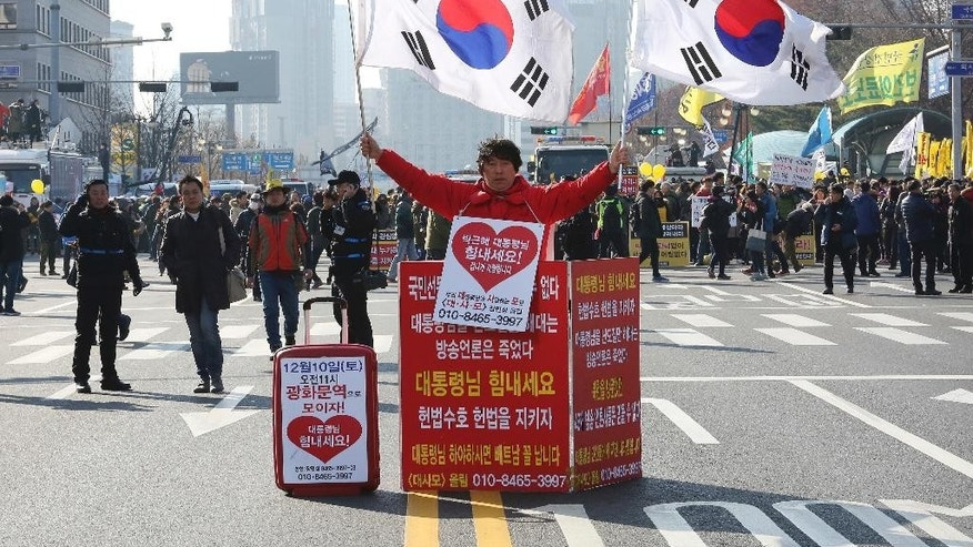 "A supporter of South Korean President Park Geun-hye holds the national flags during a rally opposing the parliamentary impeachment of Park in front of the National Assembly in Seoul, South Korea, Friday, Dec. 9, 2016. Park entered what could be her last day in power Friday, as lawmakers geared up for what's widely expected to be a successful impeachment vote amid a corruption scandal that has left her isolated and loathed. The signs read ""Oppose the impeachment."" (AP Photo/Ahn Young-joon)"