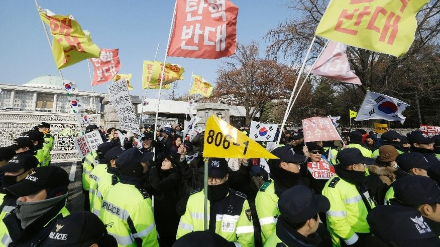 "Supporters of South Korean President Park Geun-hye are surrounded by police officers during a rally opposing the parliamentary impeachment of Park in front of the National Assembly in Seoul, South Korea, Friday, Dec. 9, 2016. Park entered what could be her last day in power Friday, as lawmakers geared up for what's widely expected to be a successful impeachment vote amid a corruption scandal that has left her isolated and loathed. The sign read ""Oppose the impeachment. "" (AP Photo/Ahn Young-joon)"
