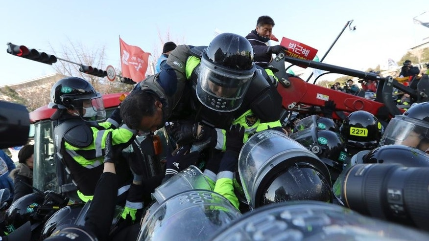 Police officers try to drag down protesting farmers from their tractors as they are blocked by police officers before a rally demanding the impeachment of South Korean President Park Geun-hye in front of the National Assembly in Seoul, South Korea, Friday, Dec. 9, 2016. Park entered what could be her last day in power Friday, as lawmakers geared up for what's widely expected to be a successful impeachment vote amid a corruption scandal that has left her isolated and loathed. (AP Photo/Lee Jin-man)