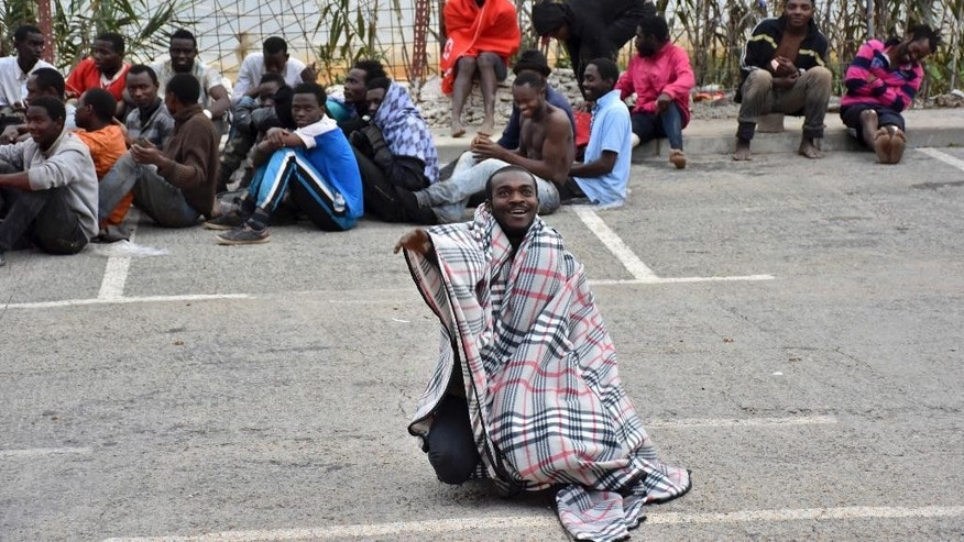 Migrants sit on the ground after storming a fence to enter the Spanish enclave of Ceuta, Spain Friday Dec. 9, 2016. The Interior Ministry says some 400 migrants from Africa have stormed a border fence to enter Spain's North African enclave of Ceuta from Morocco early Friday. (AP Photo/Jose Antonio Sempere)