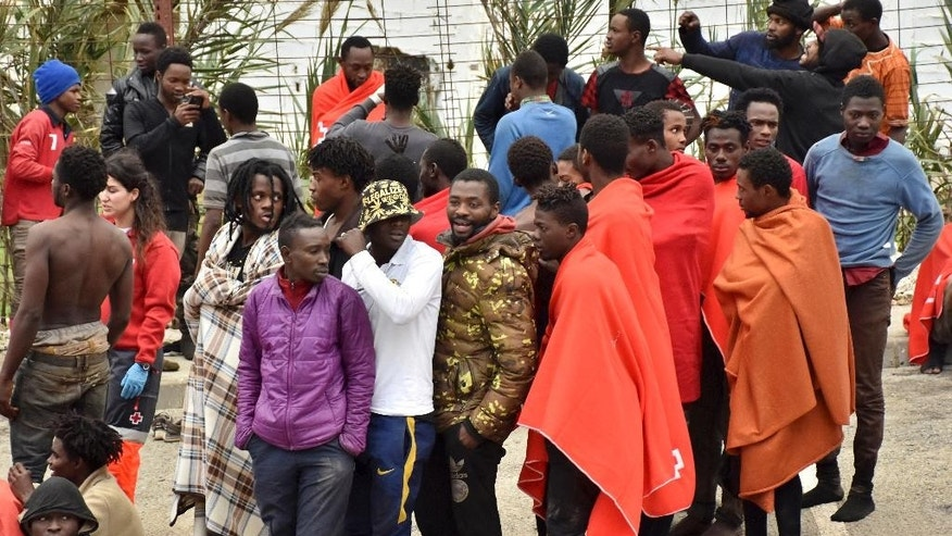 Migrants stand together after storming a fence to enter the Spanish enclave of Ceuta, Spain Friday Dec. 9, 2016. The Interior Ministry says some 400 migrants from Africa have stormed a border fence to enter Spain's North African enclave of Ceuta from Morocco early Friday. (AP Photo/Jose Antonio Sempere)