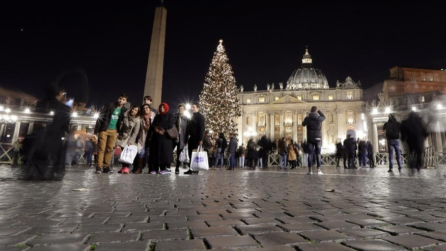 People pose for a photograph in front a the lit Christmas Tree and nativity scene in St. Peter's Square, at the Vatican, Friday, Dec. 9, 2016. (AP Photo/Andrew Medichini)