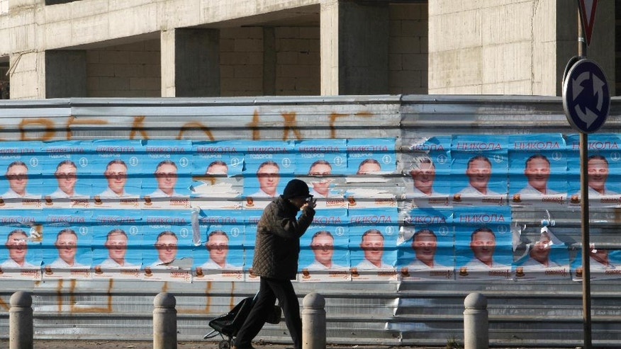 A man walks past election posters of the ruing VMRO-DPMNE party, set on a fence along a street in Macedonia's capital Skopje, Friday, Dec. 9, 2016. Eleven political parties and coalitions in Macedonia are ending their campaigns ahead of general elections on Sunday. (AP Photo/Boris Grdanoski)