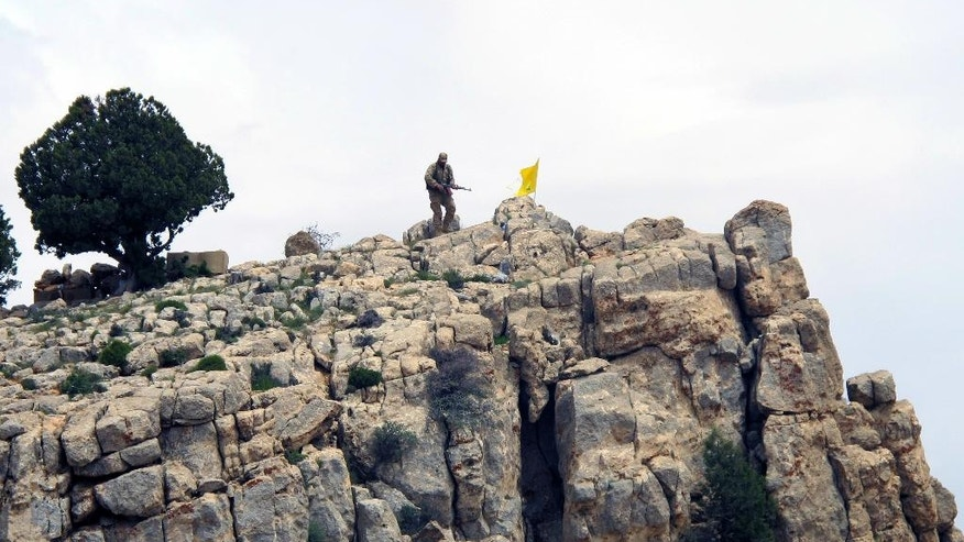FILE - In this Saturday, May 9, 2015 file photo, a Hezbollah fighter stands on a hill next to the group's yellow flag in the fields of the Syrian town of Assal al-Ward in the mountainous region of Qalamoun, Syria. Aleppo is set to be recaptured by Syrian President Bashar Assad, but the victory will not be Assad's alone. The battle for Syria's largest city has attracted thousands of foreign forces, including Russian soldiers and thousands of fighters from Iran, Lebanon, Iraq and Afghanistan. (AP Photo/Bassem Mroue, File)