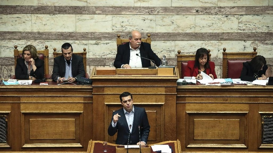 Greece's Prime Minister Alexis Tsipras, front, addresses lawmakers during a parliamentary session in Athens, Saturday, Dec. 10, 2016. Greek parliament votes on 2017 budget, as the country's left-wing government is still negotiating a new series of cost-cutting reforms that are expected to remove protection measures for private sector jobs and distressed mortgage holders. (AP Photo/Yorgos Karahalis)