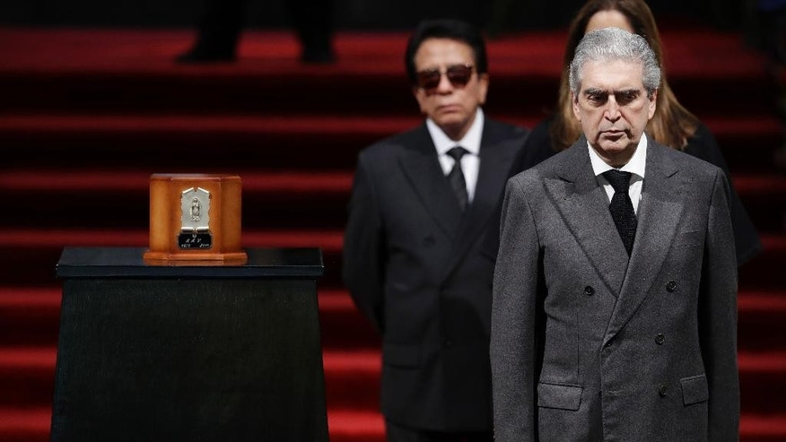 In this Sept. 5, 2016 photo, The Mexican Secretary of Culture Rafael Tovar y Teresa stands vigil beside an urn containing the ashes of Mexican music superstar Juan Gabriel during Gabriel's public memorial in the Palace of Fine Arts in Mexico City. Tovar, a diplomat, historian and promoter of the arts, died Saturday, Dec. 10, 2016 at age 62, the Culture Ministry announced. (AP Photo/Rebecca Blackwell)