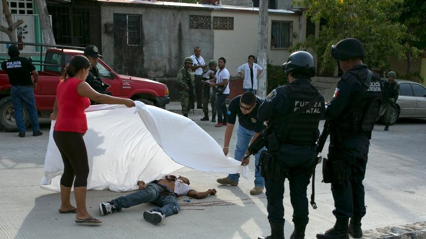 FILE - In this April 15, 2016 file photo, a forensic officer helps a woman place a sheet over the body of Alejandro Gallardo Perez, 23, after he was shot dead near his home in San Agustin, on the outskirts of Acapulco, in the Mexican state of Guerrero.  The man was shot by unknown gunmen. Ten years after it began, Mexico's drug war has done little to reduce the amount of crime or violence in Mexico's roughest regions. (AP Photo/Enric Marti, File)