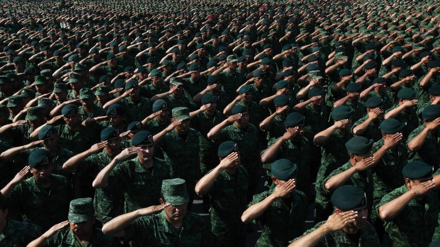 FILE - In this April 16, 2016 file photo, soldiers salute Mexico's Defense Secretary Gen. Salvador Cienfuegos at the Number 1 military camp in Mexico City. Cienfuegos noted the army's presence in Mexico's drug war was supposed to be temporary, while new, reliable police forces were built. Ten years later, that hasn't happened. (AP Photo/Marco Ugarte, File)
