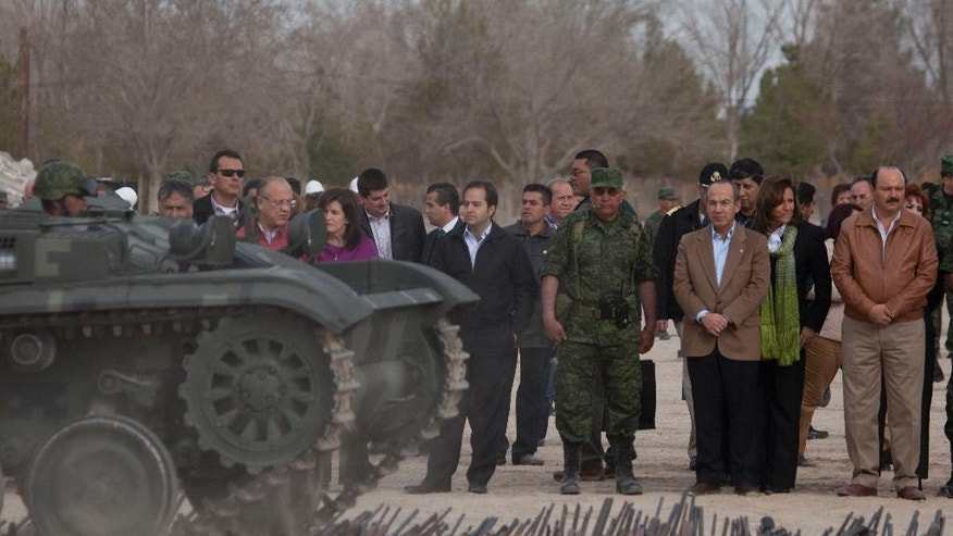 FILE - In this Feb. 16, 2012 file photo, Mexico's President Felipe Calderon, second right, watches a military vehicle roll over a stack of weapons seized from common criminals and drug traffickers, in Ciudad Juarez, Mexico. Calderon unleashed the war on drugs on Dec. 11, 2006. Some have called it a necessary but flawed effort, and others, an unneeded tragedy. (AP Photo/Eduardo Verdugo, File)