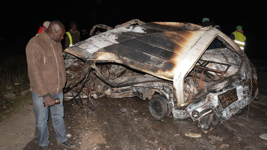 A man looks at the wreckage of a passenger minibus following an accident near Naivasha, Kenya Sunday, Dec. 11, 2017. A tanker carrying chemical gas slammed into other vehicles and burst into flames on a major road in Kenya, officials said Sunday. (AP Photo)