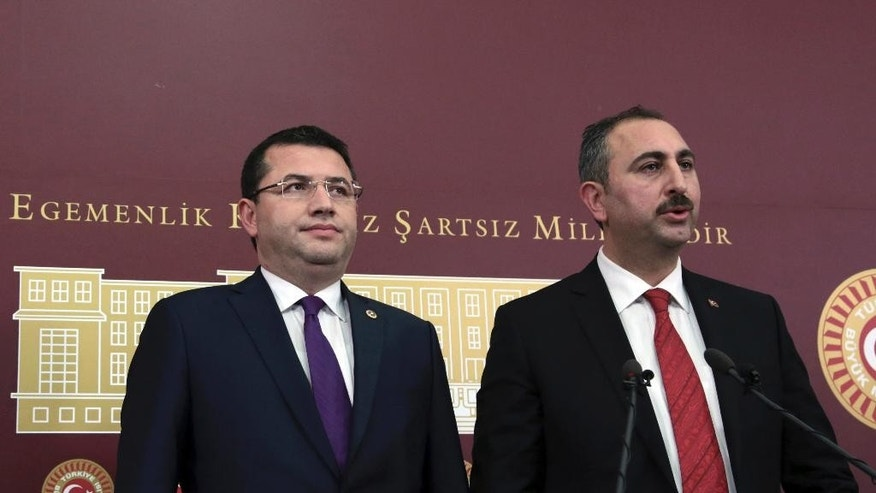 Ruling Justice and Development Party, AKP, lawmaker Abdulhamit Gul, right, and opposition Nationalist Movement Party, MHP, lawmaker Mehmet Parsak speak to the media at the parliament in Ankara, Turkey, Saturday, Dec. 10, 2016.  Turkey's ruling party submitted a constitutional amendment bill to parliament in a move that could expand the powers and extend the mandate of the country's president.  (AP Photo/Burhan Ozbilici)