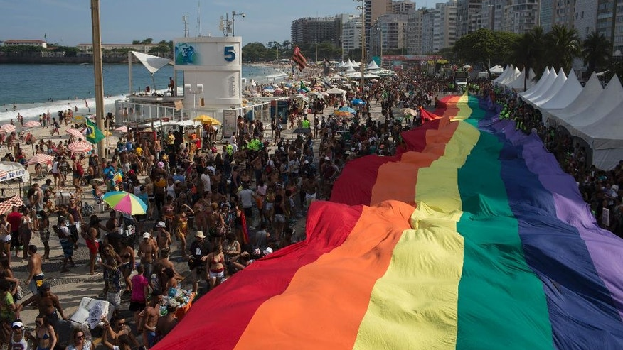 People carry a giant gay movement flag during the Gay Pride Parade at Copacabana beach in Rio de Janeiro, Brazil, Sunday, Dec. 11, 2016. People took part in Rio de Janeiro's 21st Gay Pride Parade to fight for more justice and inclusive society which recognizes equal rights for the gay community. (AP Photo/Leo Correa)