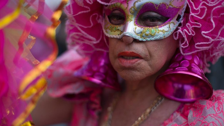 A man poses for the picture during the Gay Pride Parade at Copacabana beach in Rio de Janeiro, Brazil, Sunday, Dec. 11, 2016. People took part in Rio de Janeiro's 21st Gay Pride Parade to fight for more justice and inclusive society which recognizes equal rights for the gay community. (AP Photo/Leo Correa)