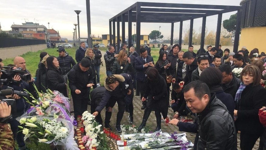 Chinese community mourners lay flowers and candles to remember 20-year-old Chinese aspiring fashion designer, Zhang Yao, 20, arrived in the Italian capital from her homeland, China, in March to attend Rome's Academy of the Fine Arts, and found dead last Friday in the Tor Sapienza area of Rome, during a commemoration Sunday, Dec. 11, 2016. (Domenico Palesse/ANSA via AP)